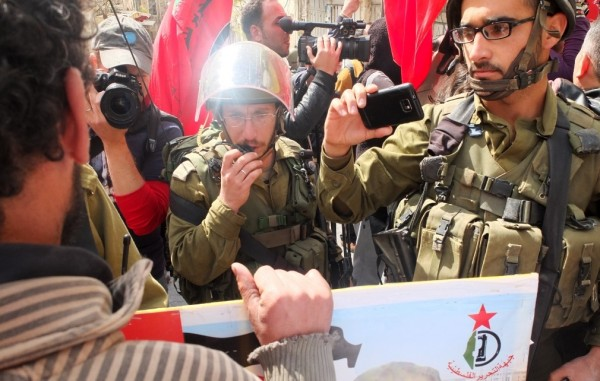 Israeli Occupation Forces stand in between peaceful demonstrators