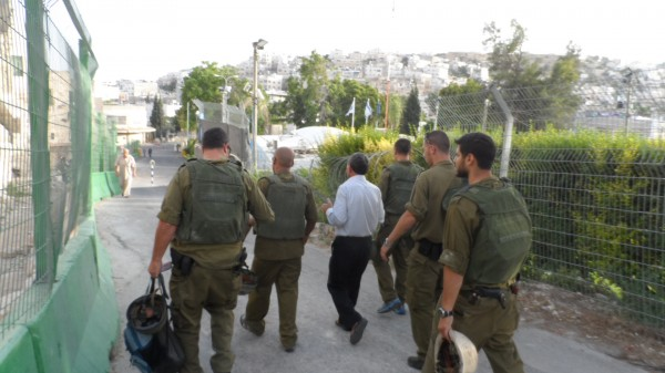 Five soldiers escort Jabari to the police van (Photo by ISM)