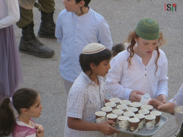 Israeli settlers and soldiers sharing tea at the scene of the execution of Fadel al-Qawasmeh