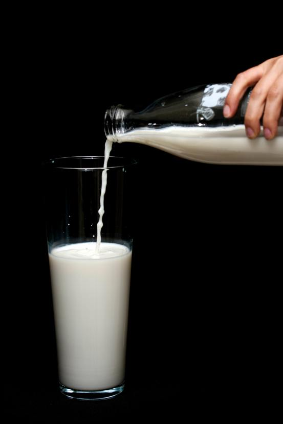 person-pouring-milk-in-highball-glass-1435706