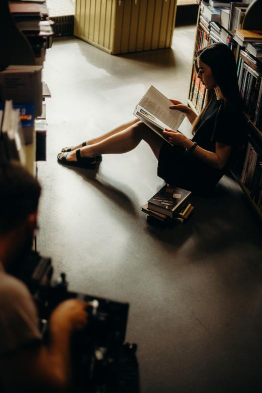 woman-sitting-on-floor-reading-book-2925303