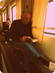 My dad reading in our soft sleeper aisle (woman on oxygen behind him)