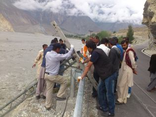 Local volunteers relocating the threatened electric poles: Photo Courtesy: Shah Wali