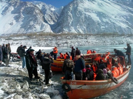 Passengers wearing the life jackets donated by FOCUS Pakistan prepare to leave in a boat this morning. Photo: Aziz Karim