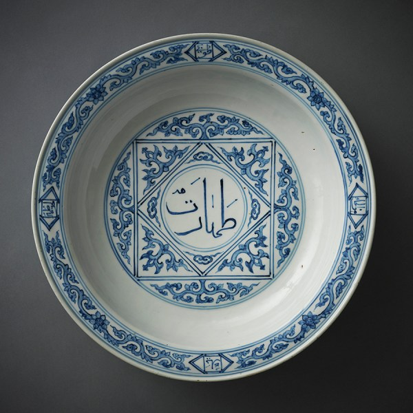 "Ablution basin: The multiple examples of sixteenth-century Chinese porcelain with Arabic inscriptions are testimony to the prominence at court of the Muslim community in China during that period, as well as the close and continuous contact between China and the Muslim world. This large dish was made in the porcelain kilns of the province of Jingdezhen in China for a Muslim patron, most probably a member of the close circle of Emperor Zhengde (reigned 1505–21) whose reign mark can be seen on the back of the dish. The word taharat (""purity"") is inscribed in Arabic in the central medallion of the dish, implying that it was meant for use in ablution, a basic requirement of Muslim prayer. The Chinese-style floral meander on the rim and its back frames several inscriptions that further evoke the concept of ritual purity and specifically mention ablution (al-wudu'). - Photo: AKDN"