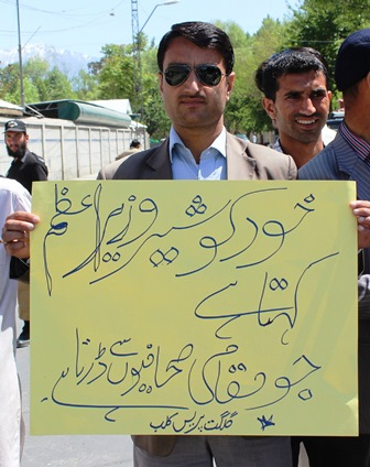 A journalist carrying a placard on which the PM has been taunted for calling himself a 'lion' and being afraid of the local journalists