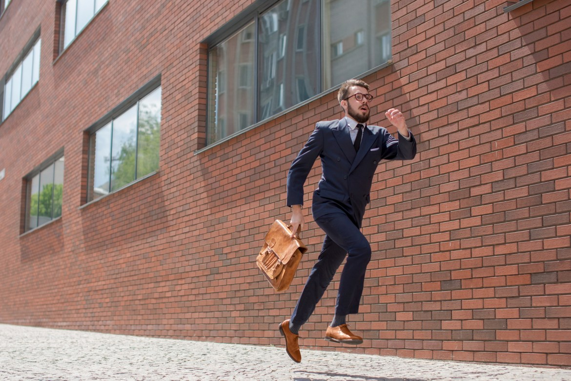 Young businessman with a briefcase and glasses running in a city street