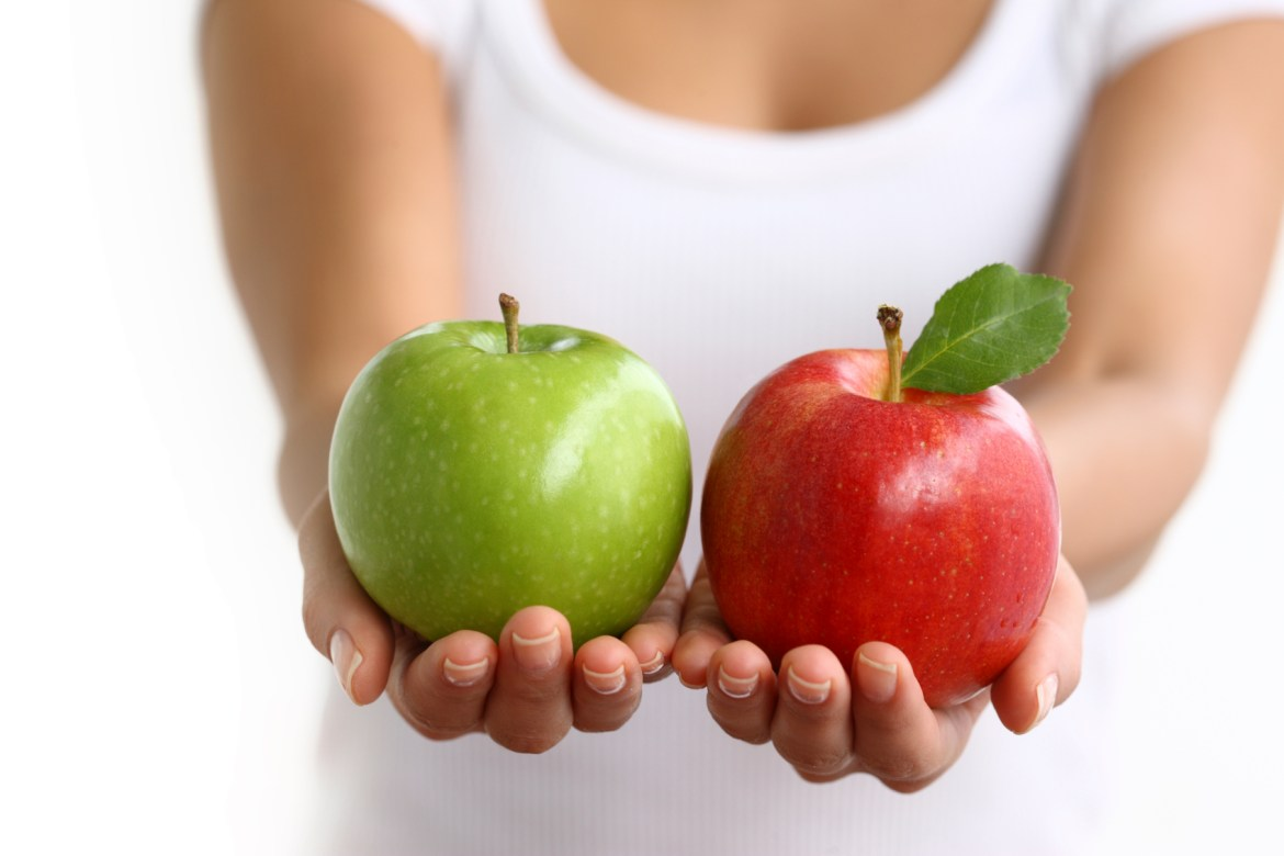 Hands holding red and green apples