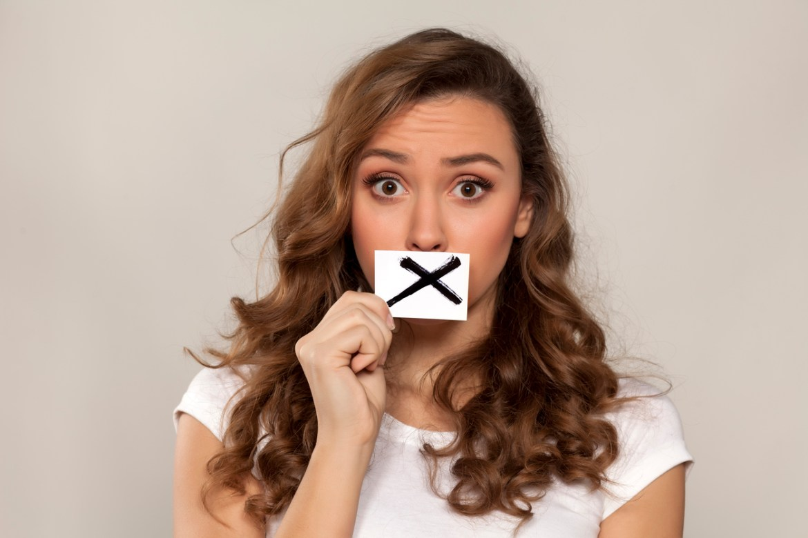 Lady holding a X over her mouth