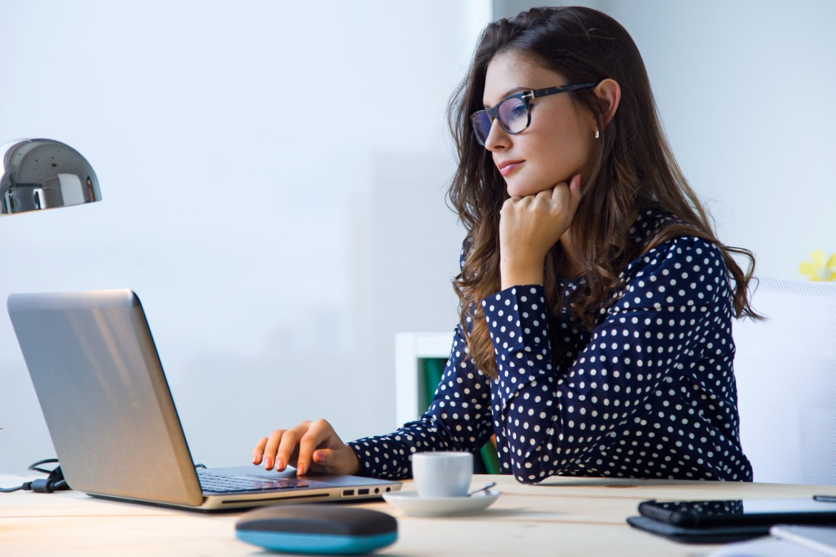 Younger lady sitting at a desk with her laptop