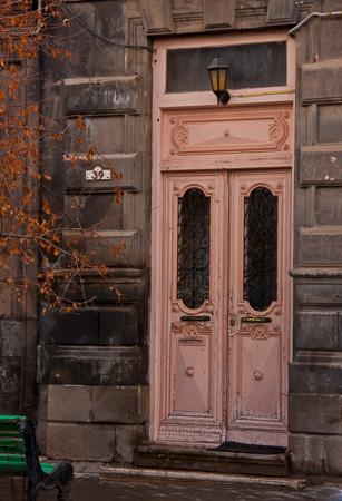 Pnk door and green bench in Gyumri