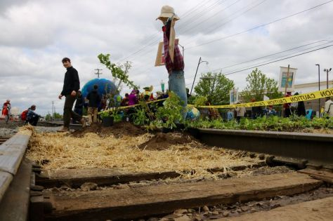 PMG PHOTO: ZANE SPARLING - Activists planted a 'Victory over fossil fuels Garden' along a BNSF rail line leading to the Zenith Energy oil terminal in Northwest Portland on Sunday, April 21.