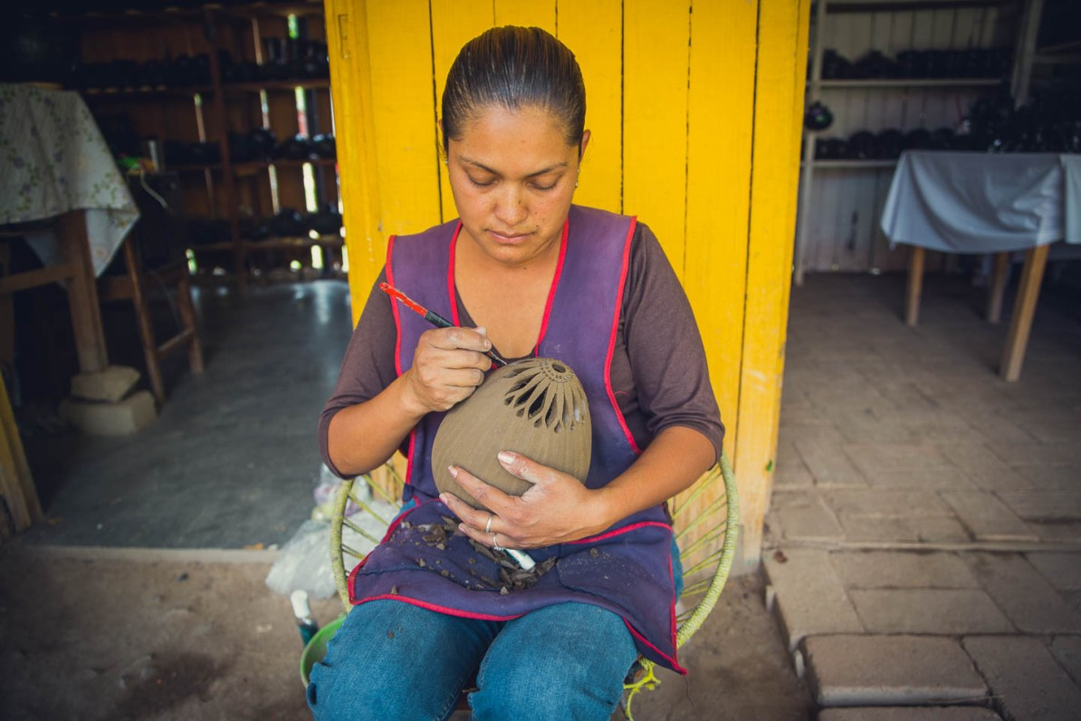 This artisan kindly offered to show us how she added the detailed lattice work to one of her black pottery designs.