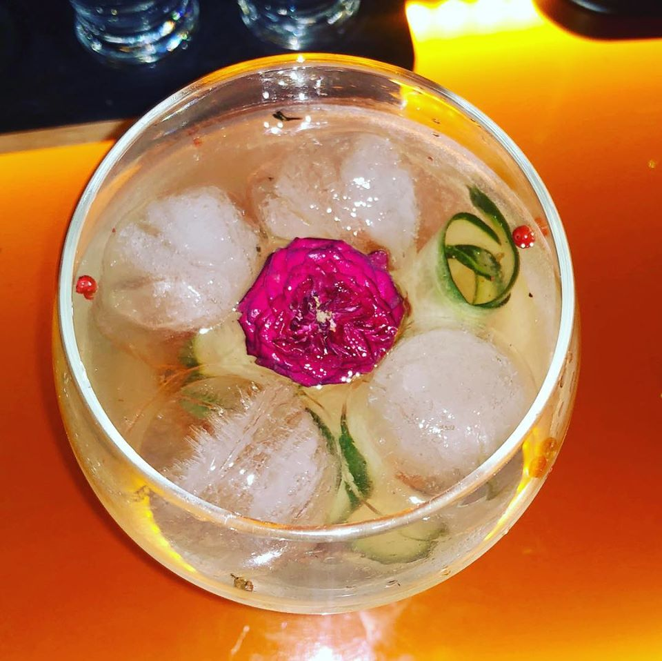 Gin cocktail with pink pepper, cucumber and edible flowers