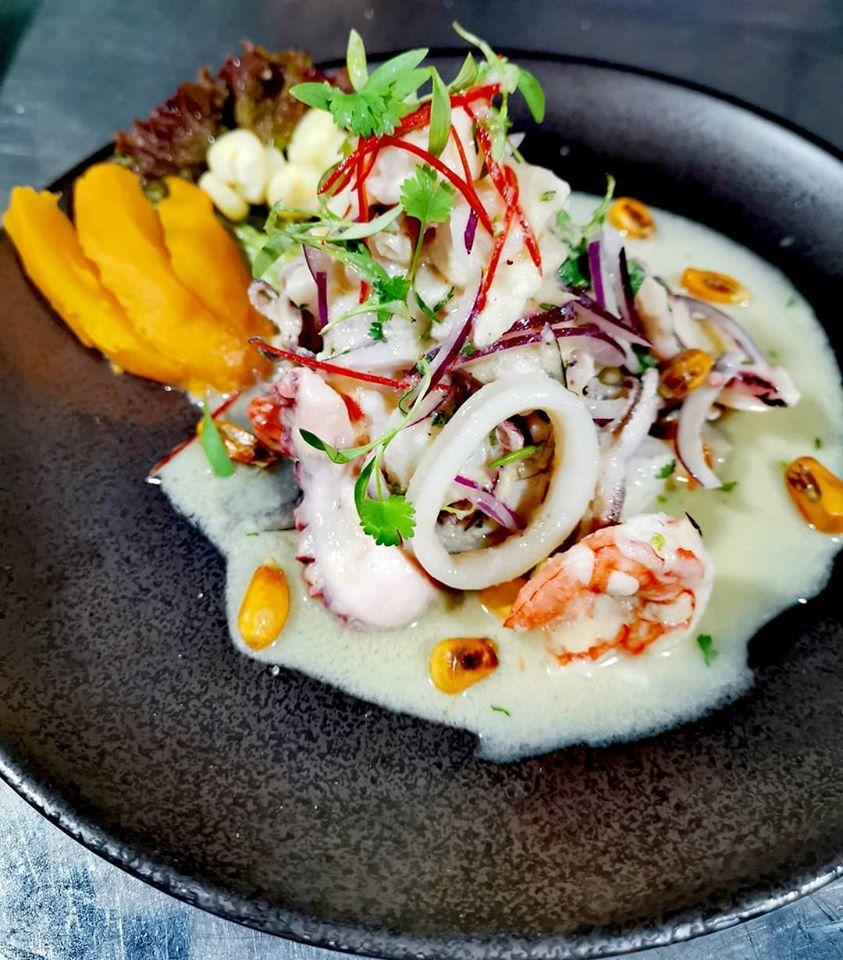 Ceviche matador con camarones, pulpo, calamares, corvina, arañitas, cebolla morada, cilantro, picante, leche de tigre camote, cancha y choclo