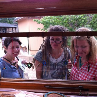 Three ladies looking into window at glassware