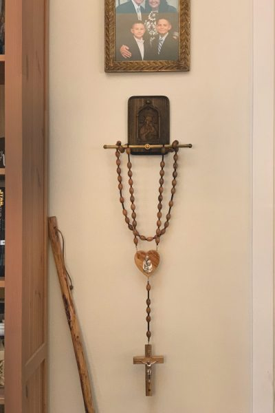 Wall rosary hanging on a vintage rosary holder.