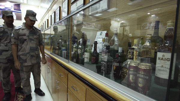 Students under training in the Drug and Poison Division of King Fahad Security College look at a collection of bottles of alcohol that Saudi security forces confiscated in the past, in Riyadh