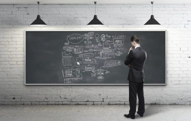 businessman looking at business strategy on blackboard