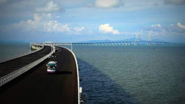"""El puente Hong Kong-Zhuhai-Macao se compone de casi 35 kilómetros de tramos de puente y carretera y un túnel de 6,7 kilómetros entre islas artificiales que permiten el paso de navíos.  El presidente Xi Jinping presidió la ceremonia de inauguración el martes. El vice primer ministro, Han Zheng, afirmó que el puente ayudaría a desarrollar un """"Área de la Gran Bahía"""" en torno al delta del río Perla, inspirada en motores económicos como la Bahía de San Francisco y la Bahía de Tokio."""