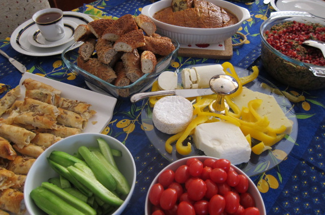 table with cucumbers, tomatoes, bread and cheese