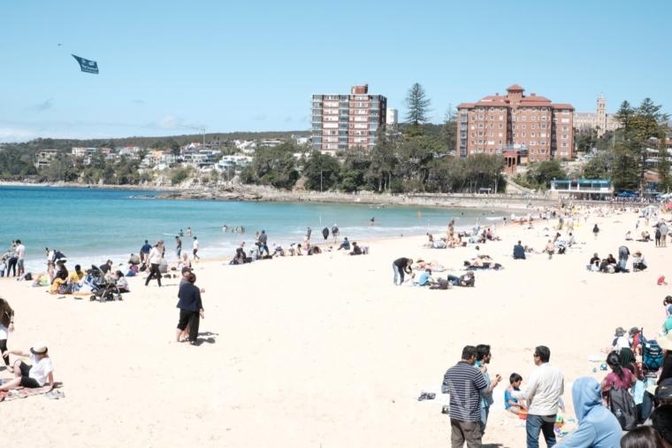 マンリービーチで日焼けを楽しむ人たち