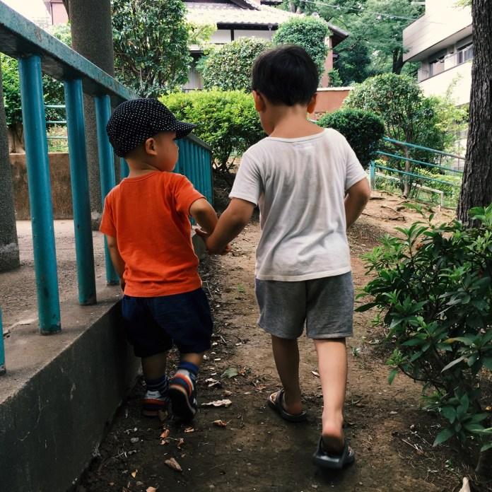 公園で手をつなぐ男の子ふたり。2歳と3歳。