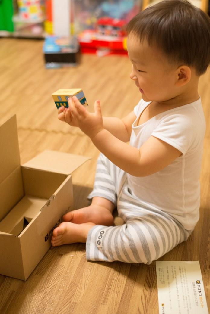 クロネコヤマトの宅急便から届きた荷物からミニカーを取り出す息子。2歳