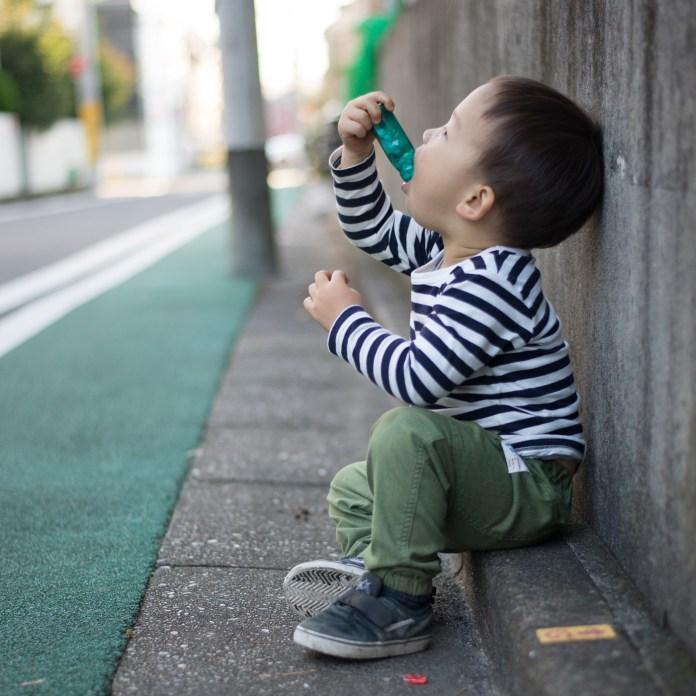 道端に座ってお菓子(ラムネ)を頬張る鼓太郎。2歳。