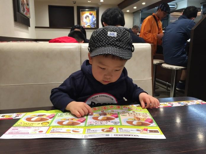 メニューを選ぶ子供(2歳)。カレーハウスCoCo壱番屋で、お子さまカレー。