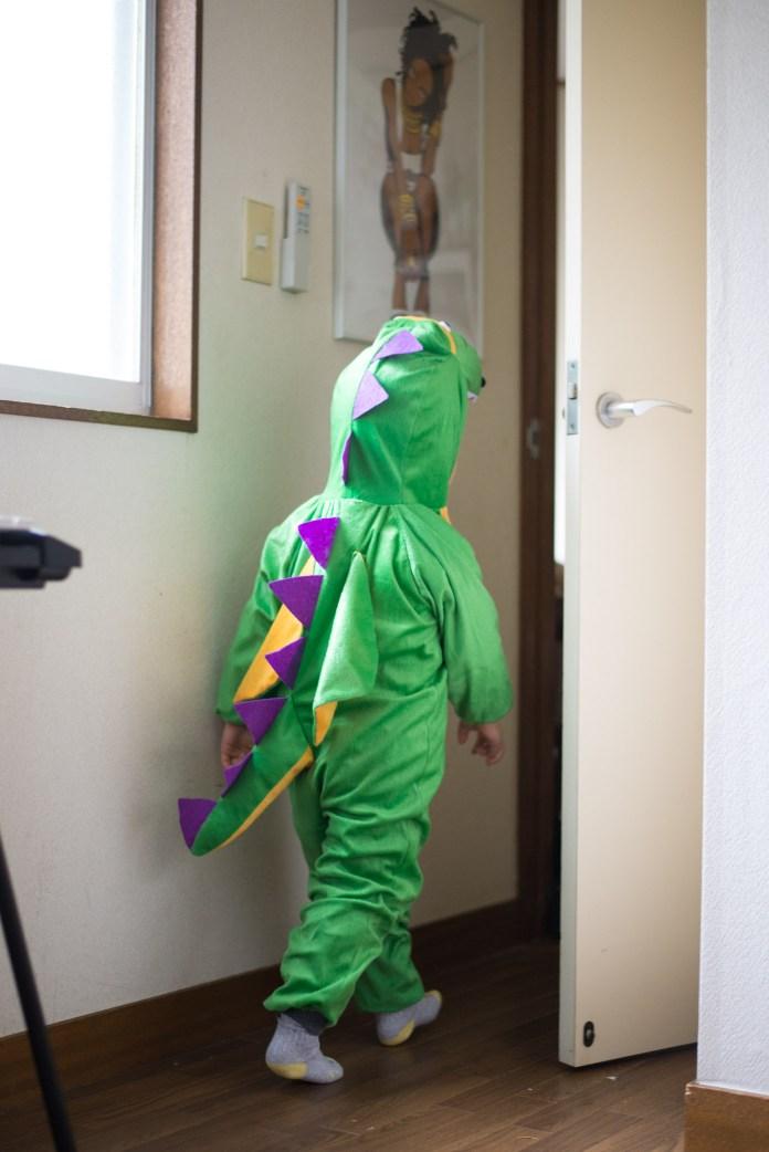 恐竜の着ぐるみを着て去ってゆく息子