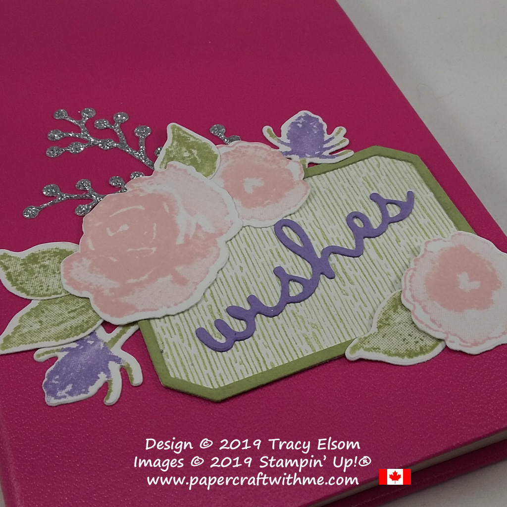 Close up of decorated hardback notebook with die-cut wishes sentiment from the Well Written Framelits and floral elements from the First Frost Stamp Set and coordinating Frosted Bouquet Framelits from Stampin' Up!.