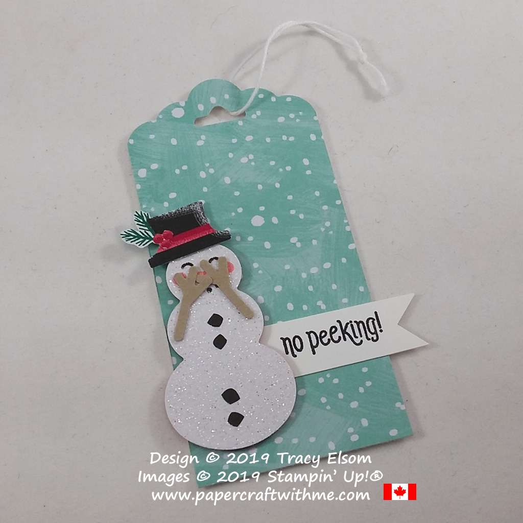 Gift tag with snowman arms positioned so he's peeking through his fingers. Created using the #Elfie Stamp Set, Let It Snow Paper and Snowman Builder Punch from Stampin' Up!