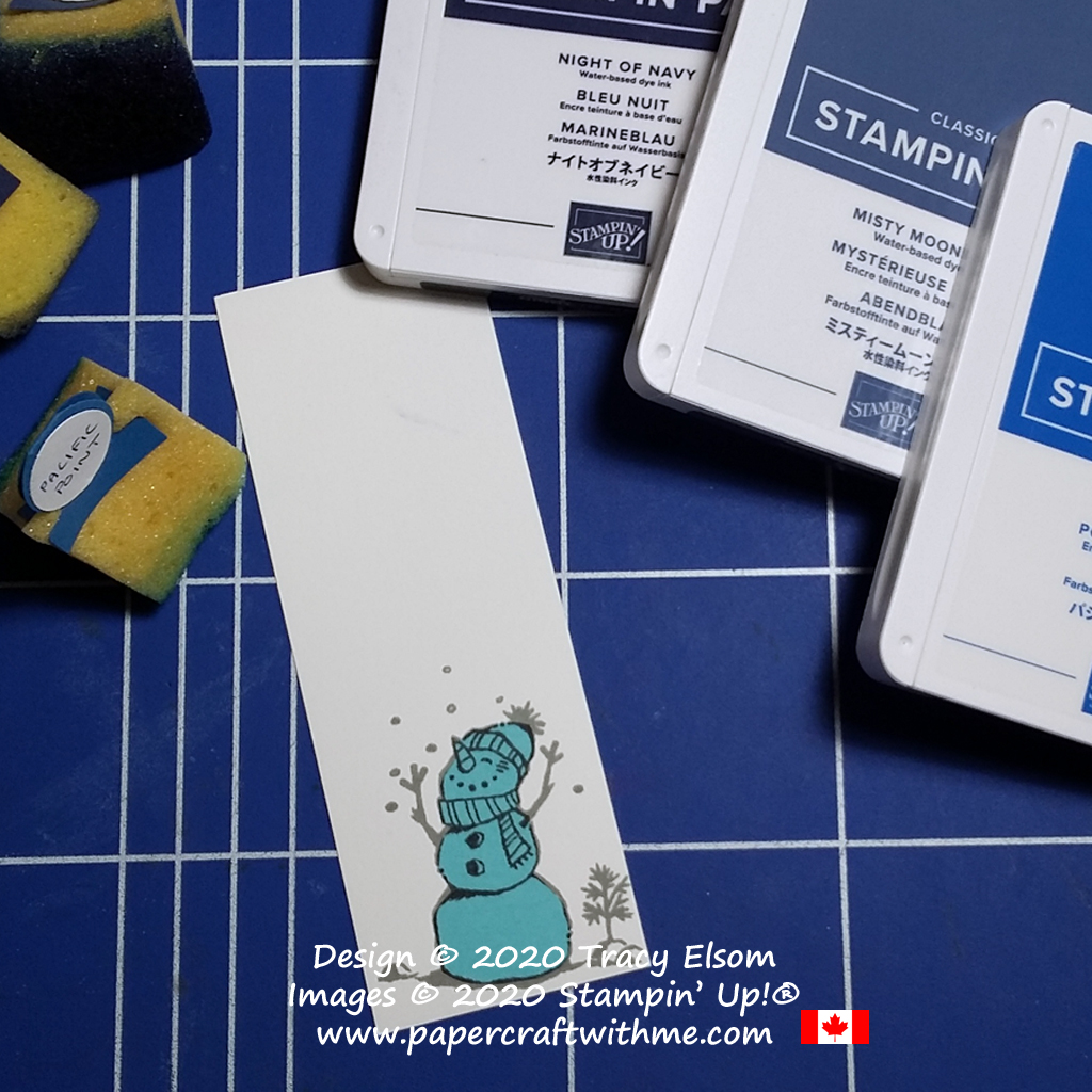 Masking a snowman from the Snowman Season Stamp Set from Stampin' Up! before sponging a snowy night scene using shades of blue ink #papercraftwithme