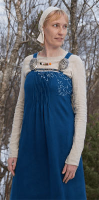 Photograph by Ingrid G. Aune Nilsen of Hilde Thunem in her reconstruction of Køstrup (grave ACQ). The white outline indicates the outline of the fabric piece found in the grave. The rest of the garment is a reconstruction. Published with permission.