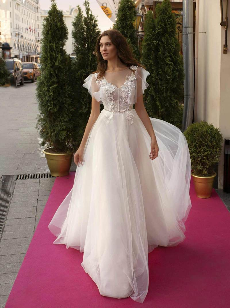 Cape sleeved wedding dress with illusion neckline and floral appliqué across the bodice