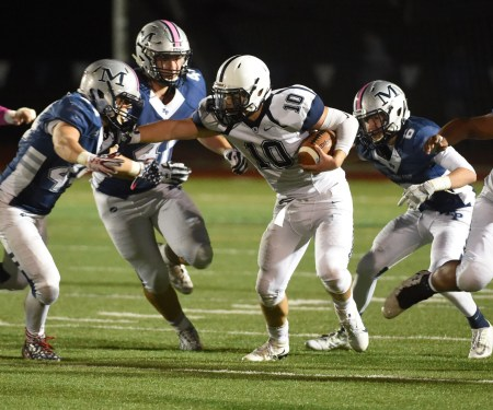 Episcopal Academy's CJ McAnally fights off Malvern Prep tacklers during a 37-34 win Friday. (Digital First Media/Pete Bannan)