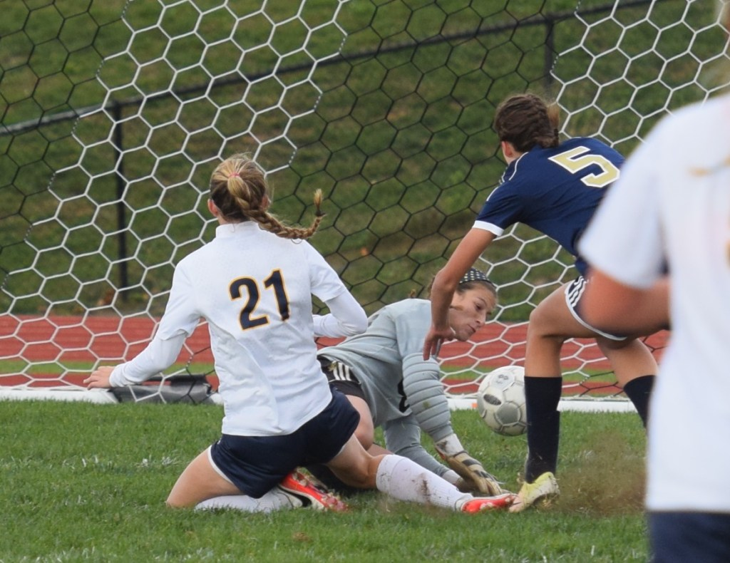 Pope John Paul II's Kayla Mesaros (21) pokes the ball past Sun Valley goalkeeper Amy Parker for her first goal during a District 1-AAA playoff game Tuesday. (Austin Hertzog - Digital First Media)