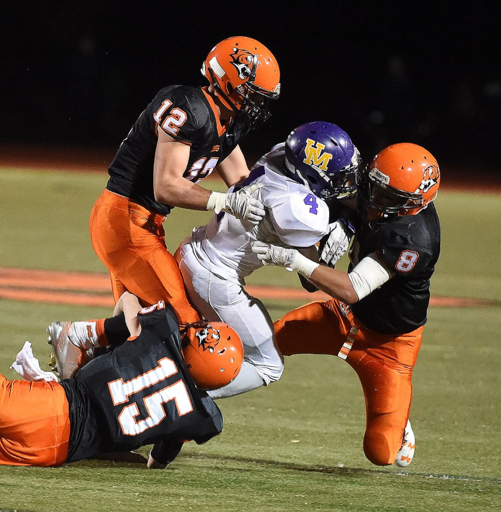 Showing the passion of a defense that dominated throughout, Marple Newtown defenders, from left, Dylan Conan, Dash Dulgerian and Carmen Christiana, swarm Upper Moreland running back Sterlen Barr in the third quarter of the Tigers' 35-7 victory Friday night. (Digital First Media/Pete Bannan)