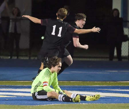 Radnor's Andrew Boujoukos, right, and Ryan Peter celebrate the former's game-winning goal in overtime past Holy Ghost Prep goalkeeper Harry Scuron as Radnor claimed the District 1 Class 3A title, 2-1. (Digital First Media/Pete Bannan)