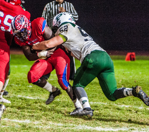 Pennridge defender Alex Schmidt (#52, right) has a hold on Neshaminy running back Will Dogba in District 1 playoff opener at Nov. 4 Harry Franks Stadium, Langhorne, Pa. (J.S. Garber – For 21st-Century Media)