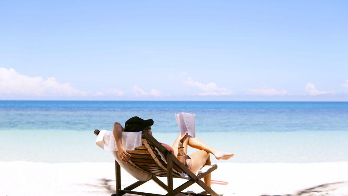 Femme avec une casquette sur la place lisant un livre en se relaxant dans une chaise longue partie grace a la conciergerie airbnb