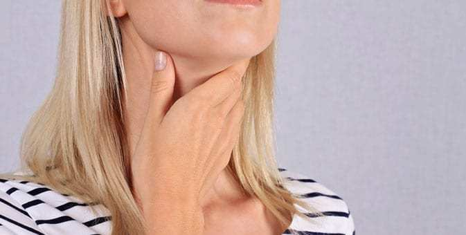 female checking her thyroid