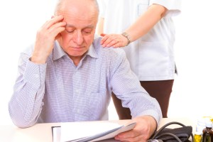 doctor comforting mature stressed patient with headache
