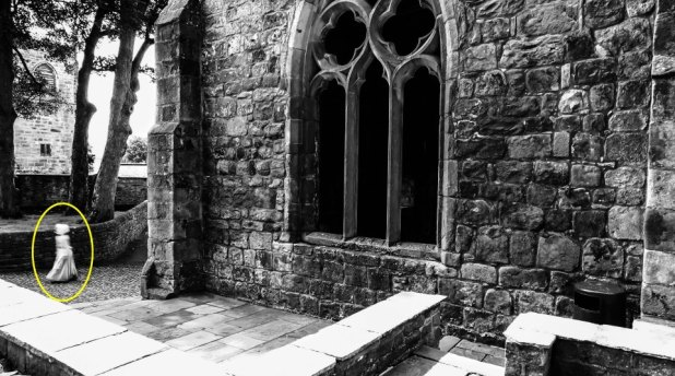 PIC FROM MERCURY PRESS (PICTURED: THE MAIN PICTURE SHOWING THE GHOST OF A LITTLE GIRL AT SKIPTON CASTLE, YORKSHIRE) A butcher has revealed a picture of what he claims is the ghost of a little girl wearing Georgian-period clothing and bonnet in the grounds of a 900-year-old castle. Mark Whitaker, 34, had visited Skipton Castle, Yorks, with his partner Amanda Ledgar, who was pregnant at the time, and had been snapping away like usual all day. It was only when he got back home in Colne, Lancs, that the then dad-to-be and now dad-of-one, noticed the three-foot tall ghostly figure walking by the castle. The image shows a clear figure in a white floor length period dress and a bonnet that appears to float where her head would be - though the eerie child has no visible arms or neck. Mark claims the image still sends a shiver down his spine whenever he looks at it but has now revealed it to see what others think. SEE MERCURY COPY