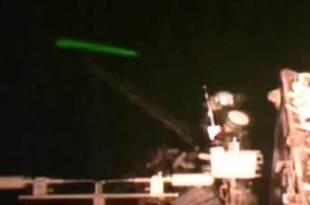 Un drone extraterrestre vert tire aux abords de la station spatiale