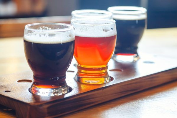 Flight with various types of craft beer in small glasses on a wooden table in a pub
