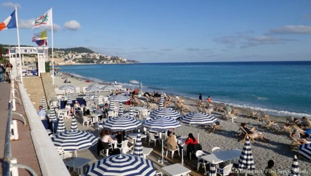 Promenade des Anglaisin alapuolella, meren rannalla sijaitseva ravintola auringonvarjoineen.