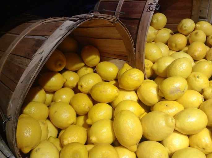 Image showing abundance of yellow, with hundreds of lemons spilling out of two barrels