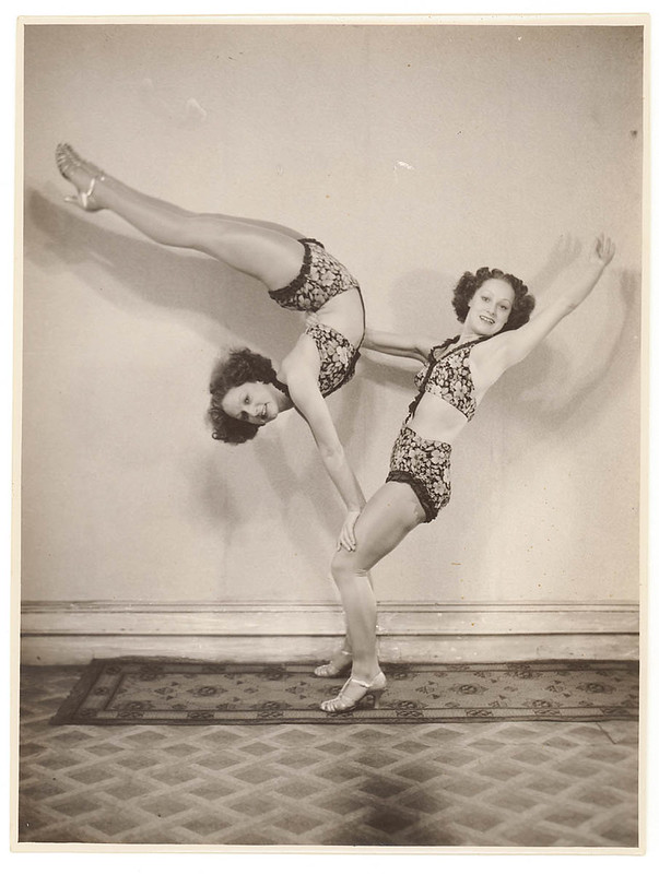 Two acrobats, one standing and supporting the entire weight of the other in the air, who is bending her legs backwards whilst resting her hands on the standing woman's knees.